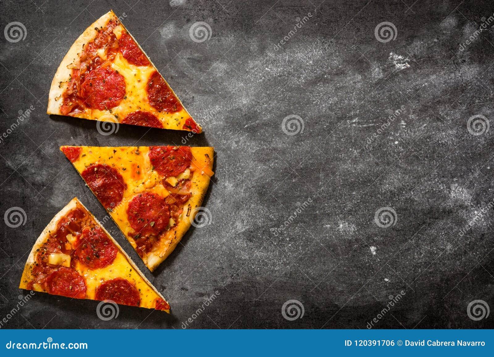 Hot italian pepperoni pizza slice on black stone.