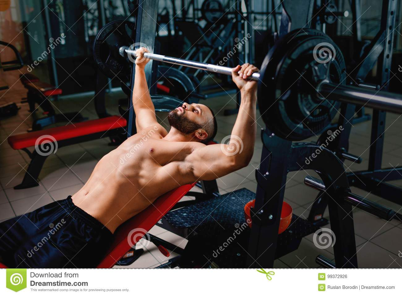 A Hot Man With Strong Muscular Body Performs A Bench Press Using A Barbell On A