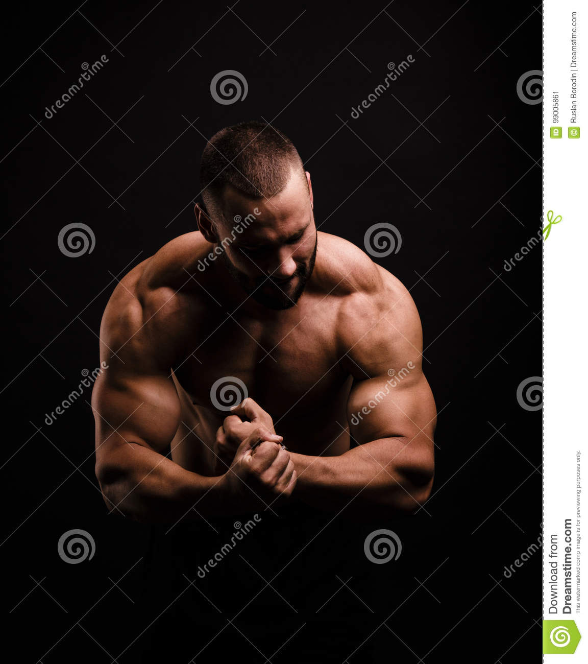 Hot muscular man on a black background. A shirtless bodybuilder showing off triceps and biceps. Hard workout concept.