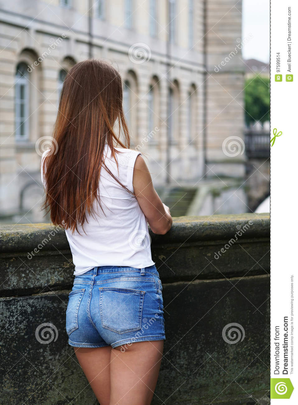 81434a0dfbb Rear view of young woman waering denim hot pants or booty shorts. fashion  trend.