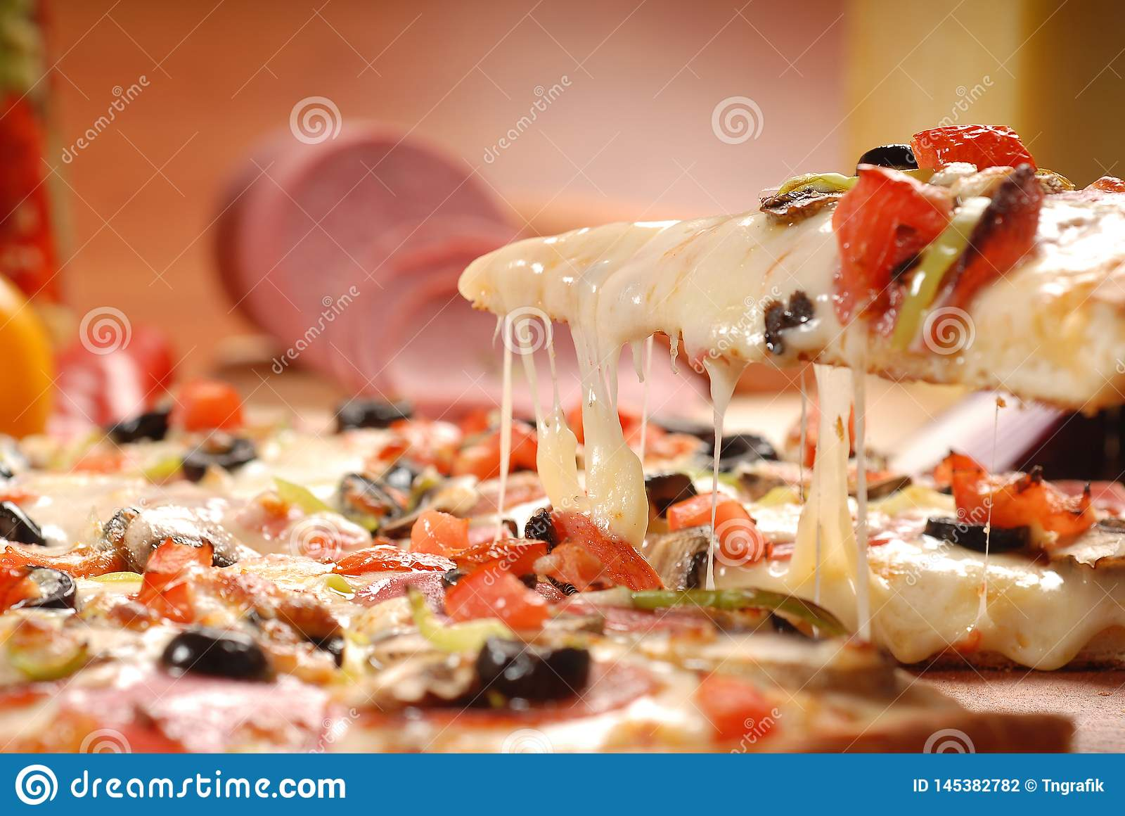 American pizza with pepperoni, mozzarella and tomato sauce. Pizza on a wooden table, morning, dawn
