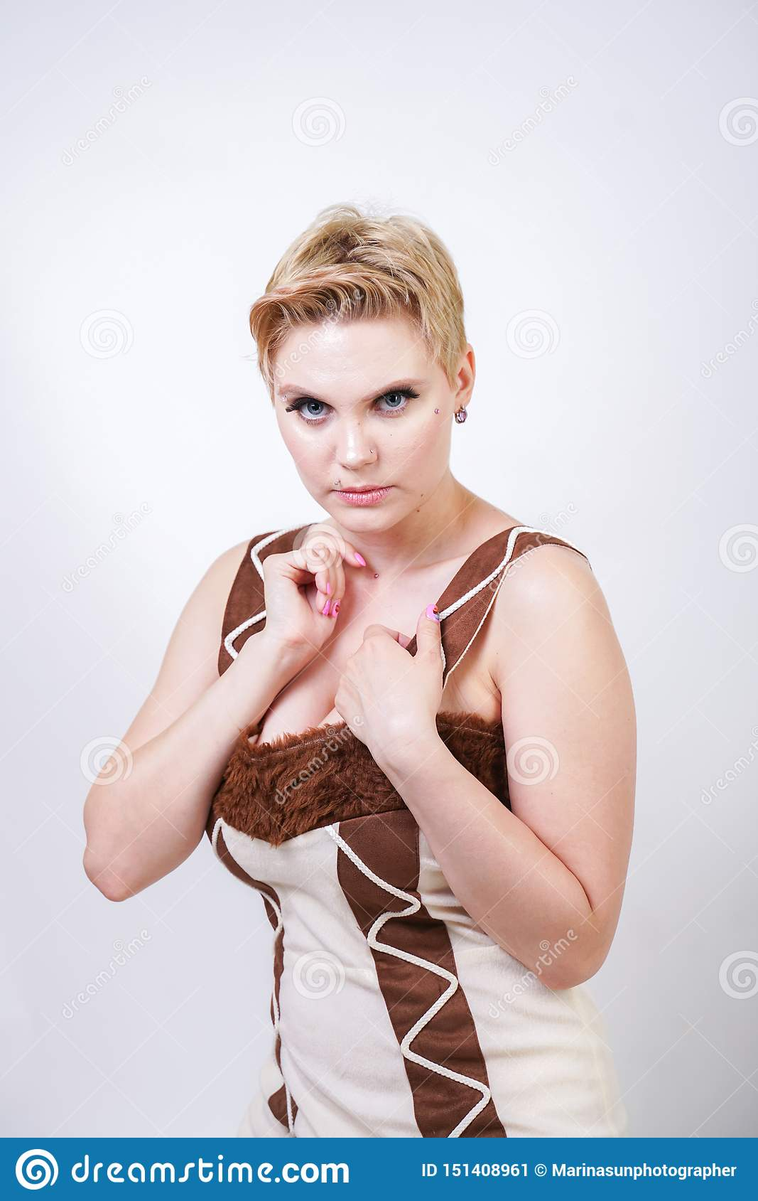 Hot plus size woman in fur carnival costume of primitive man on white background in Studio. a beautiful savage girl in a brown dre
