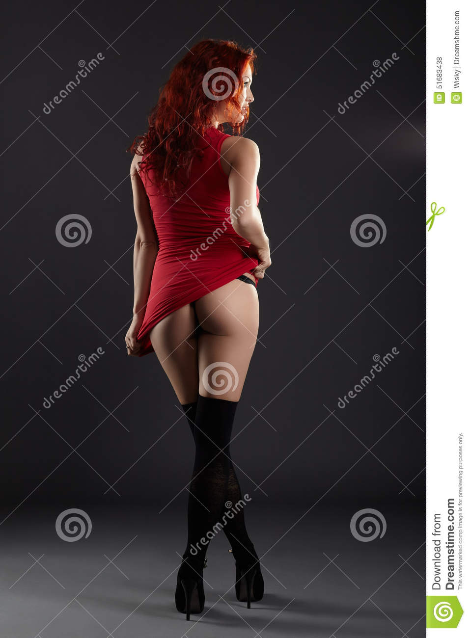 Hot red-haired woman bared her ass, on gray background