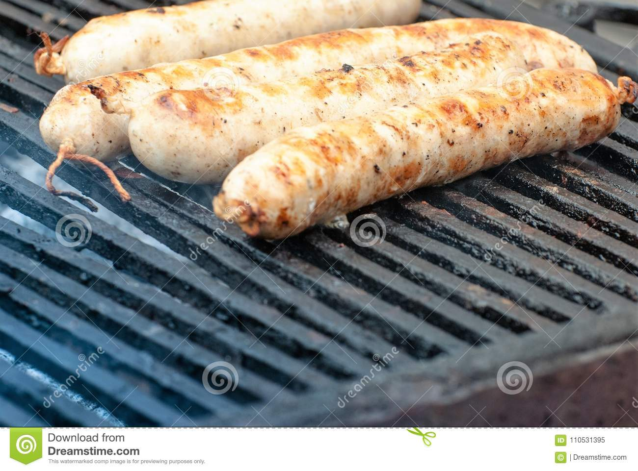Hot sausages on a barbecue with fragrant smoke.