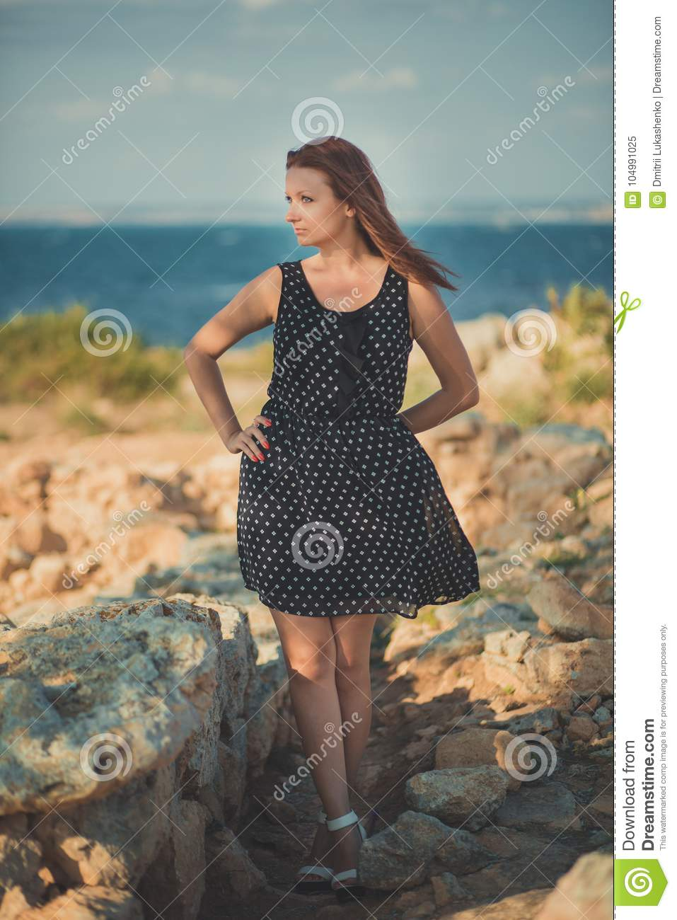 Hot stylish dressed young lady brunette hairs and pinky cheeks with open legs shoulders and arms posing sensuality on sea sid