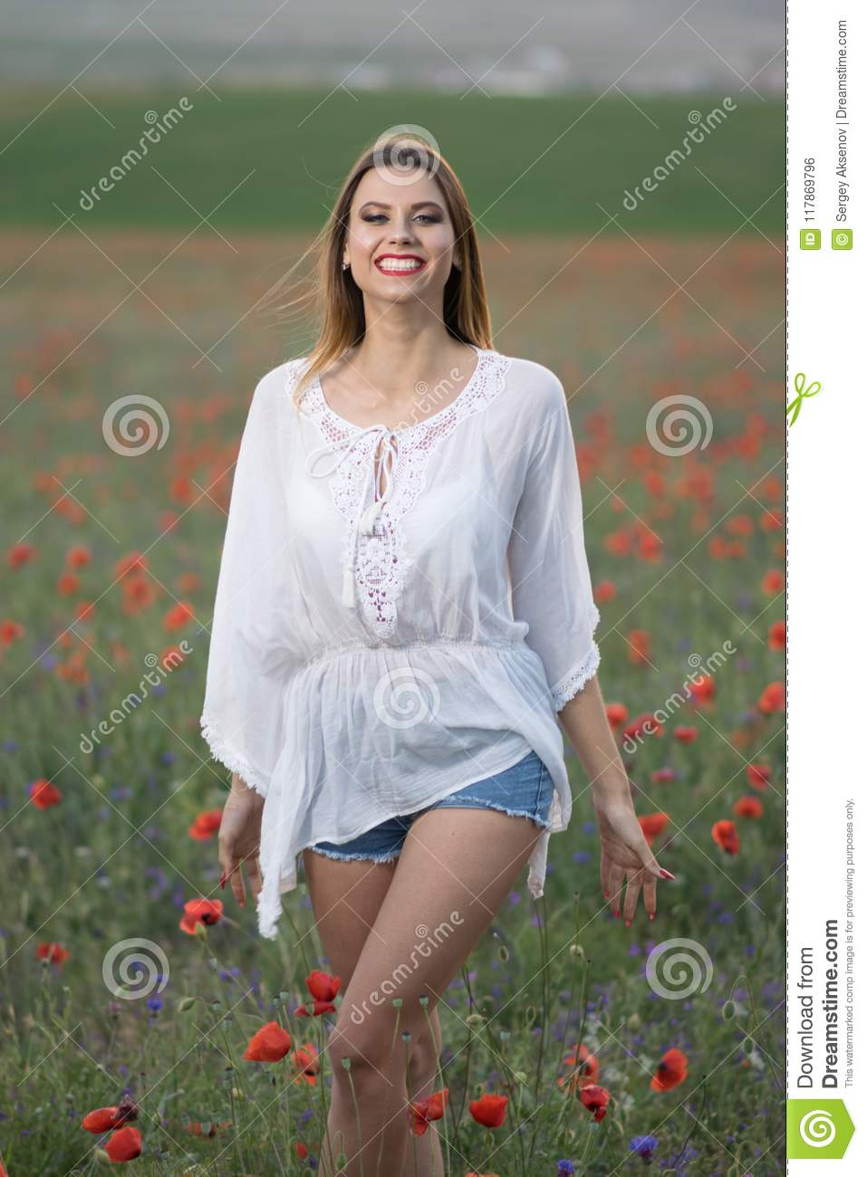Hot young woman walking among the poppies in a hat