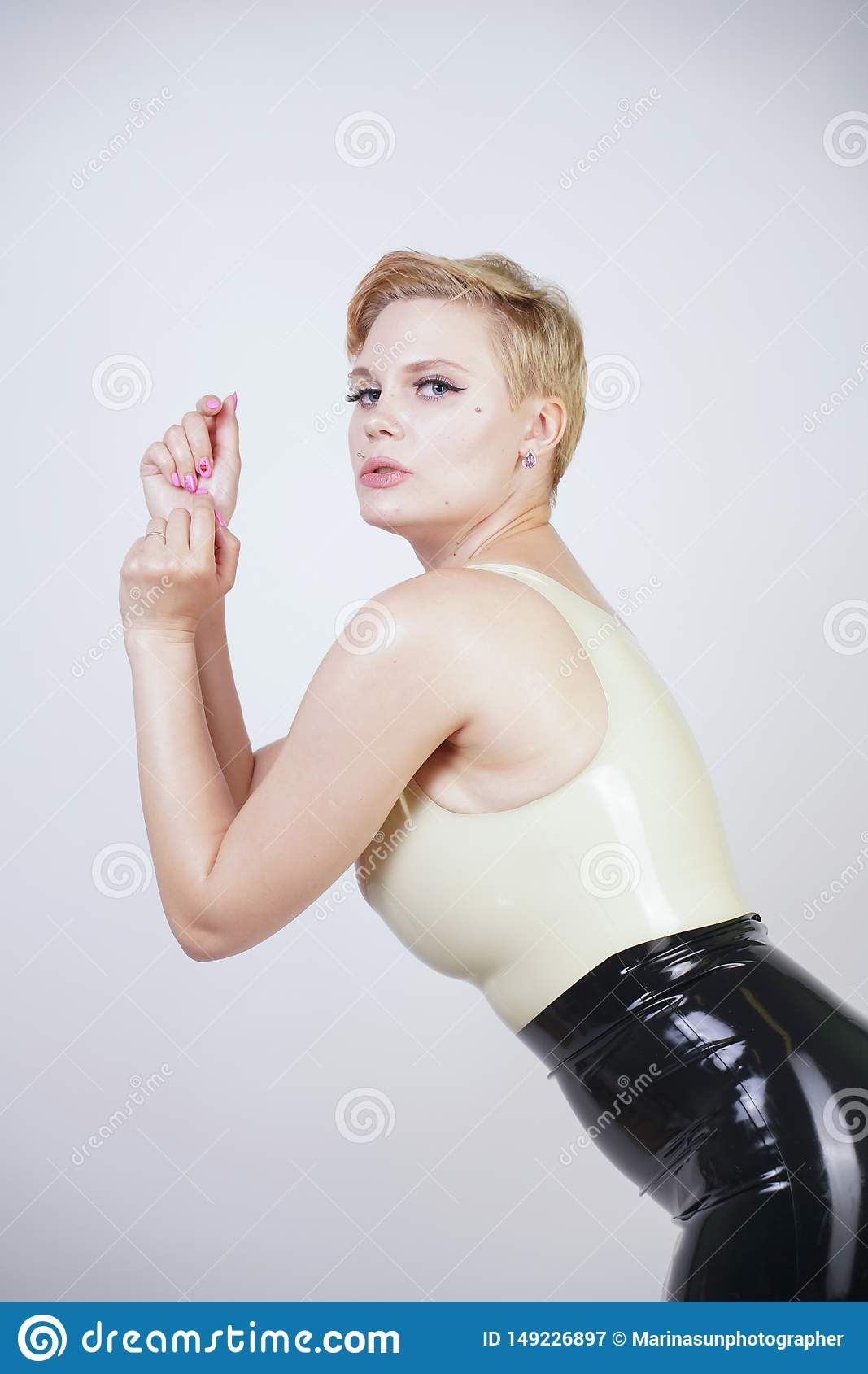 Hot short hair blonde girl with curvy body wearing latex rubber dress on white studio background