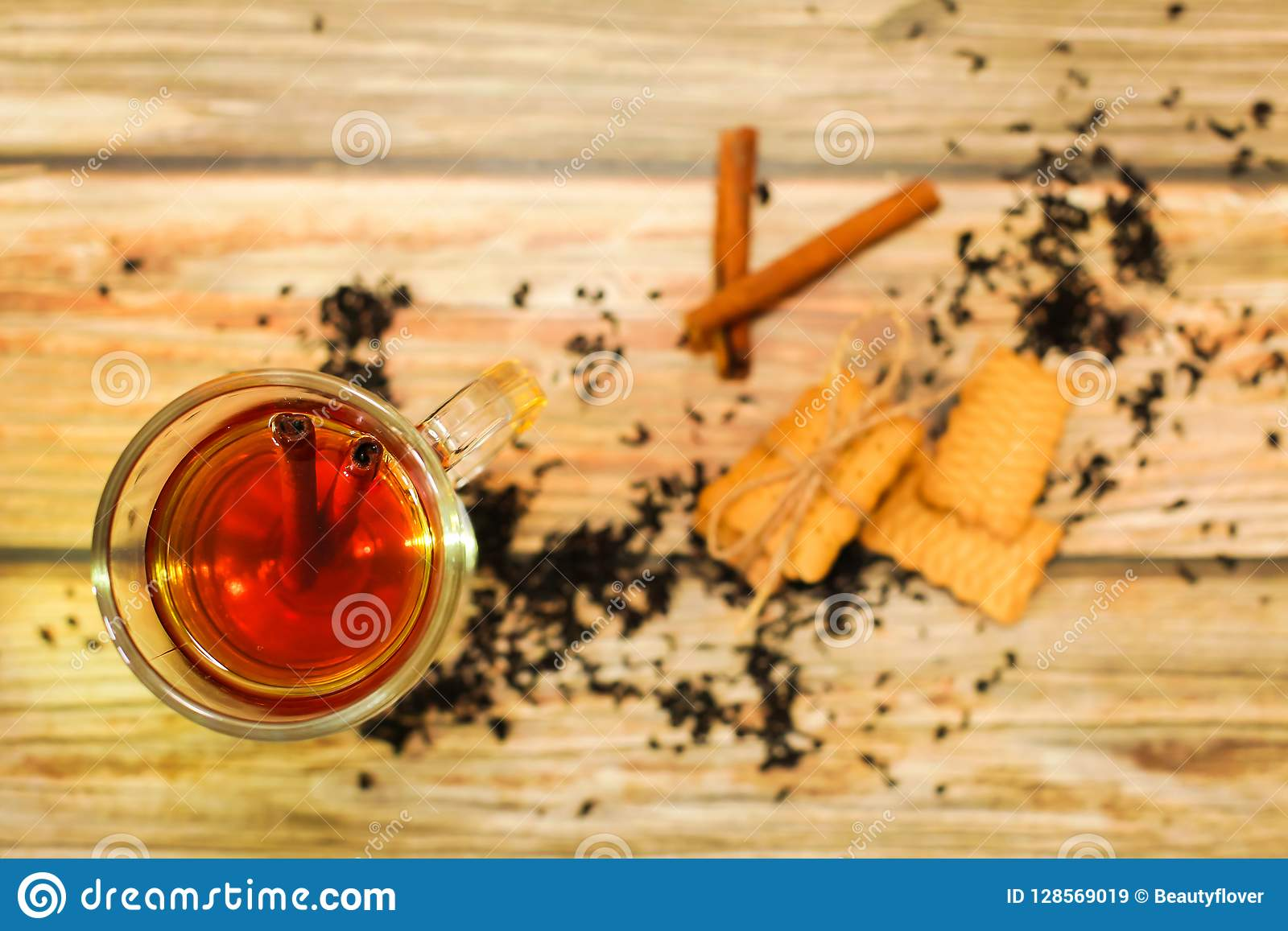 Hot Tea in glass cup with cinnamon sticks tea leaves and cookies on wooden table, flat lay