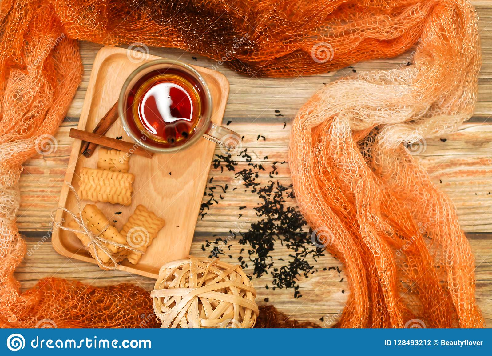 Hot Tea in glass cup with cinnamon sticks tea leaves and cookies on wooden table and knitted scarf around, flat lay