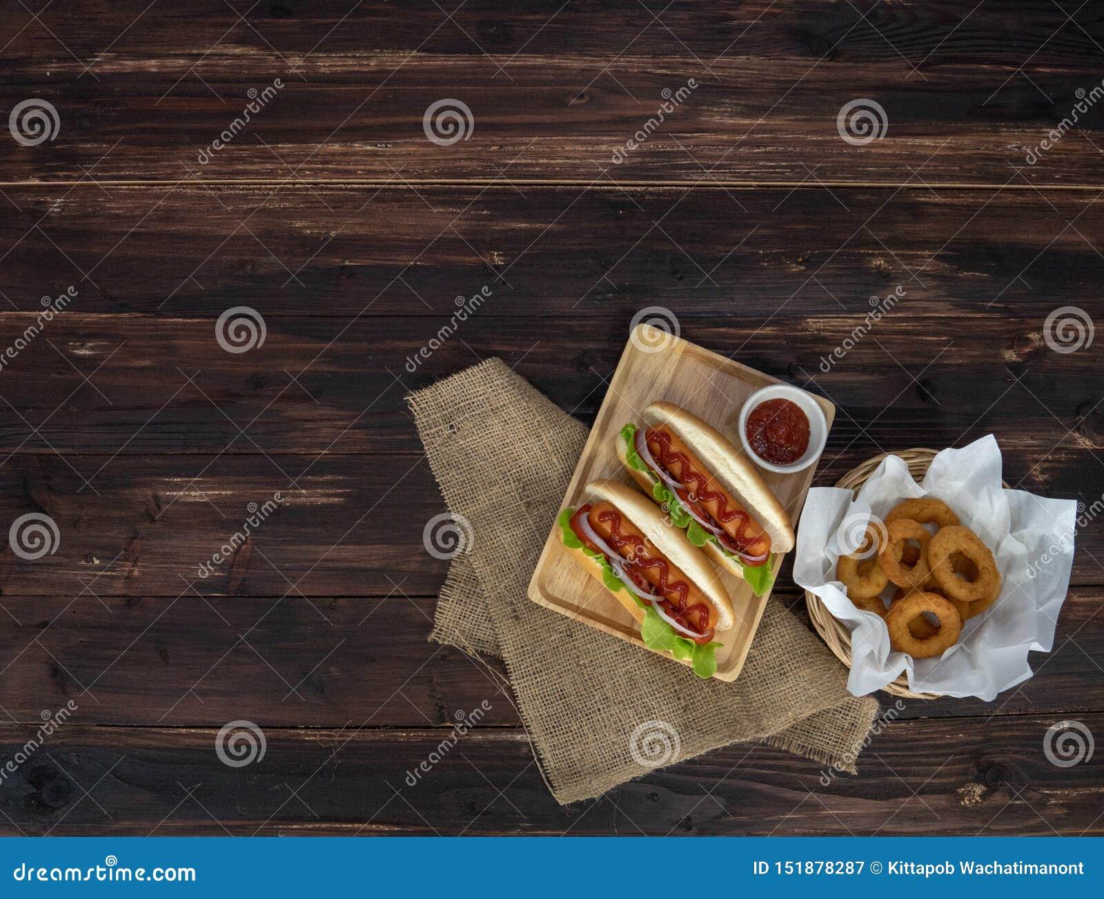 Hotdogs e anéis de cebola fritados, arranjado belamente, apetitosos na mesa de jantar de madeira marrom