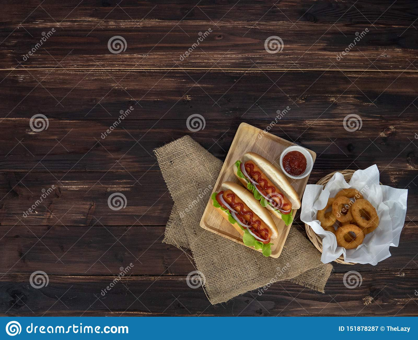 Hotdogs and fried onion rings, beautifully arranged, appetizing on the brown wooden dining table
