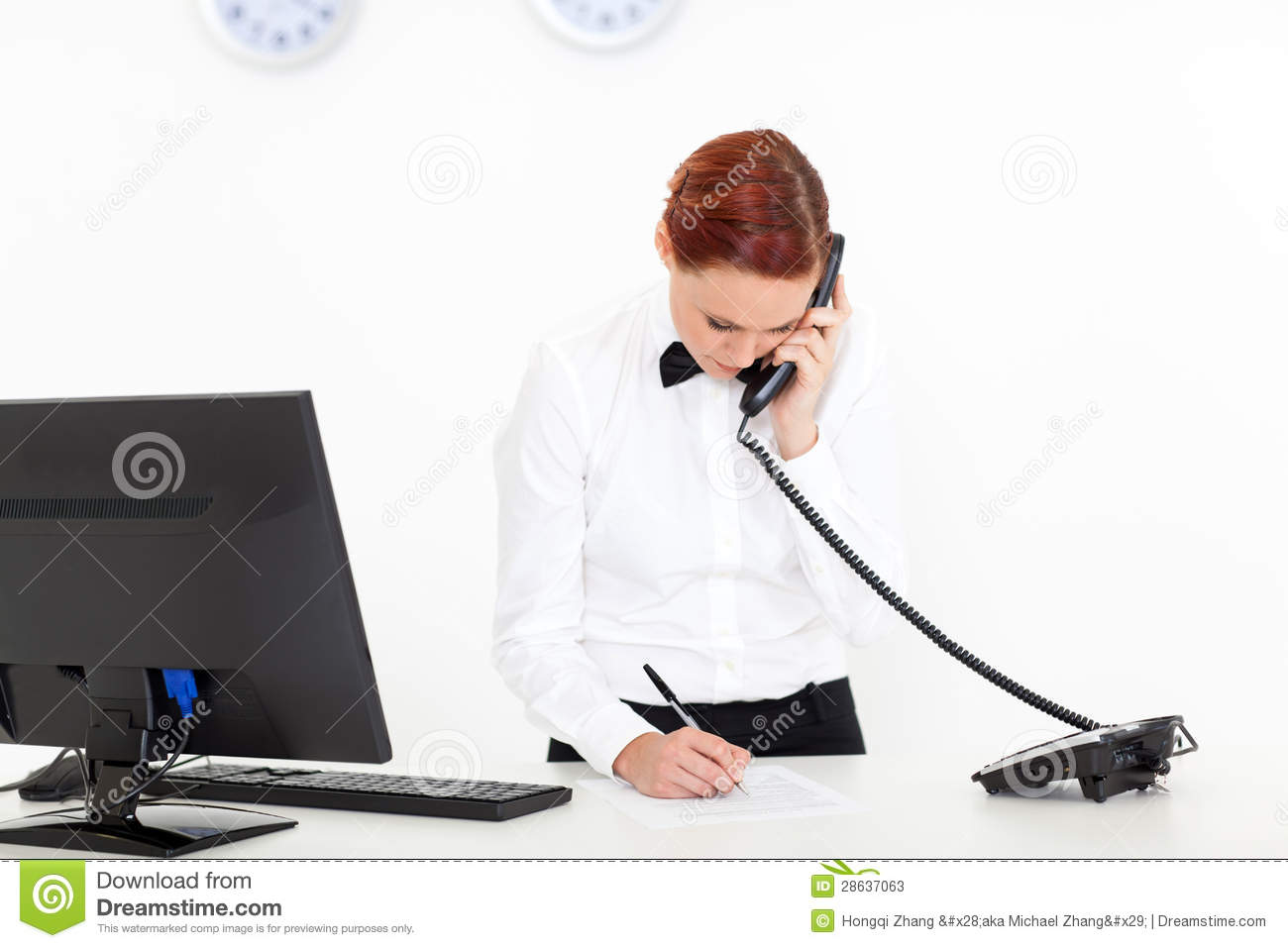 Modern hotel receptionist talking on the phone at reception.