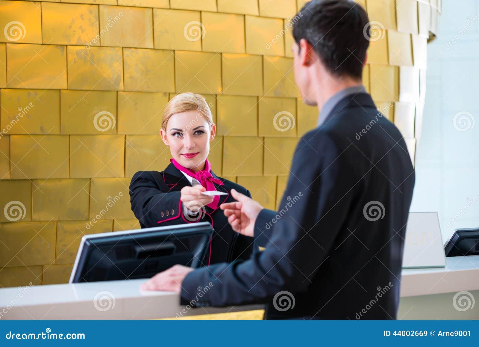 hotel receptionist check in man giving key card stock photo hotel receptionist check in man giving key card