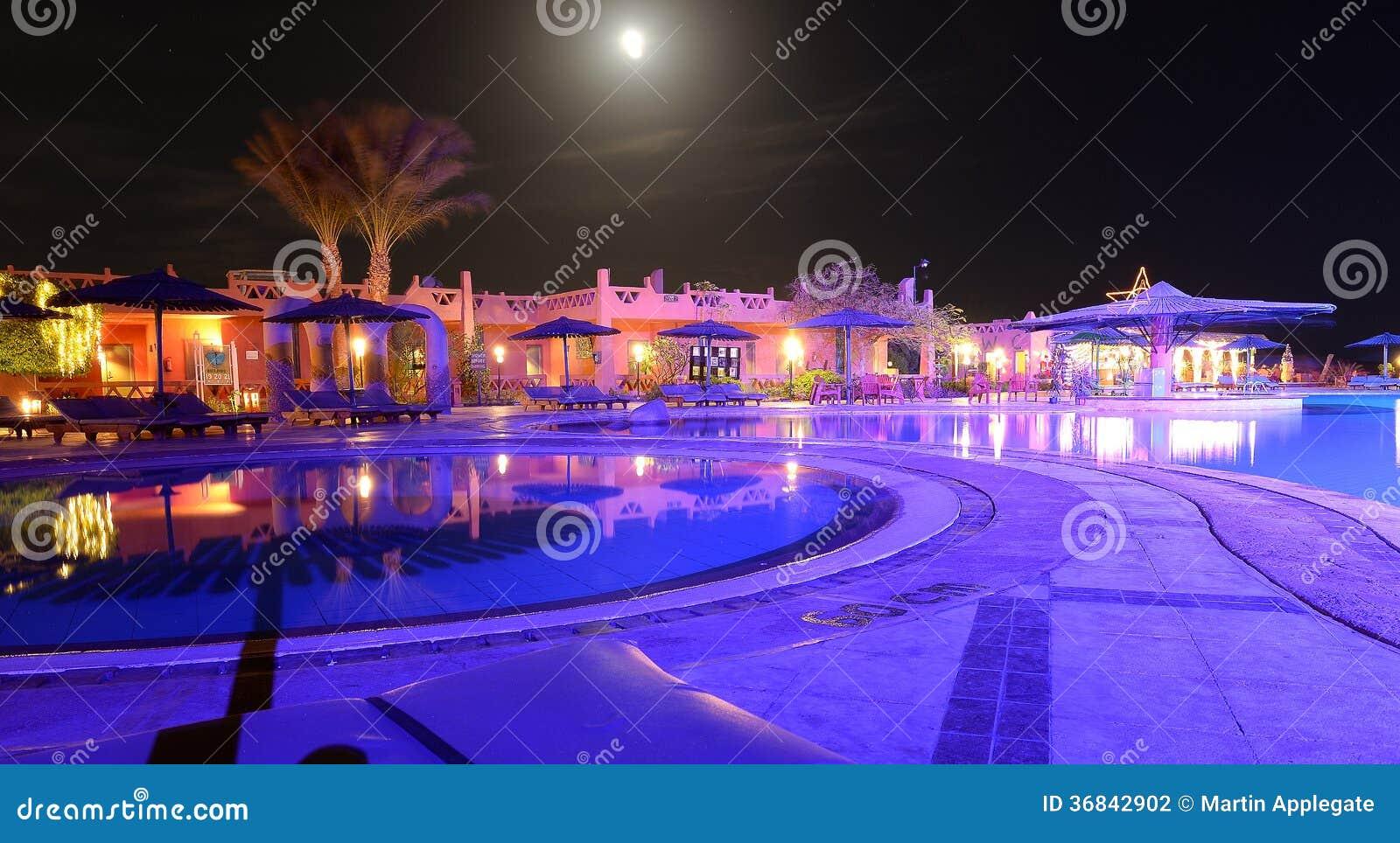 Hotel w kurorcie patio przy nocą i basen
