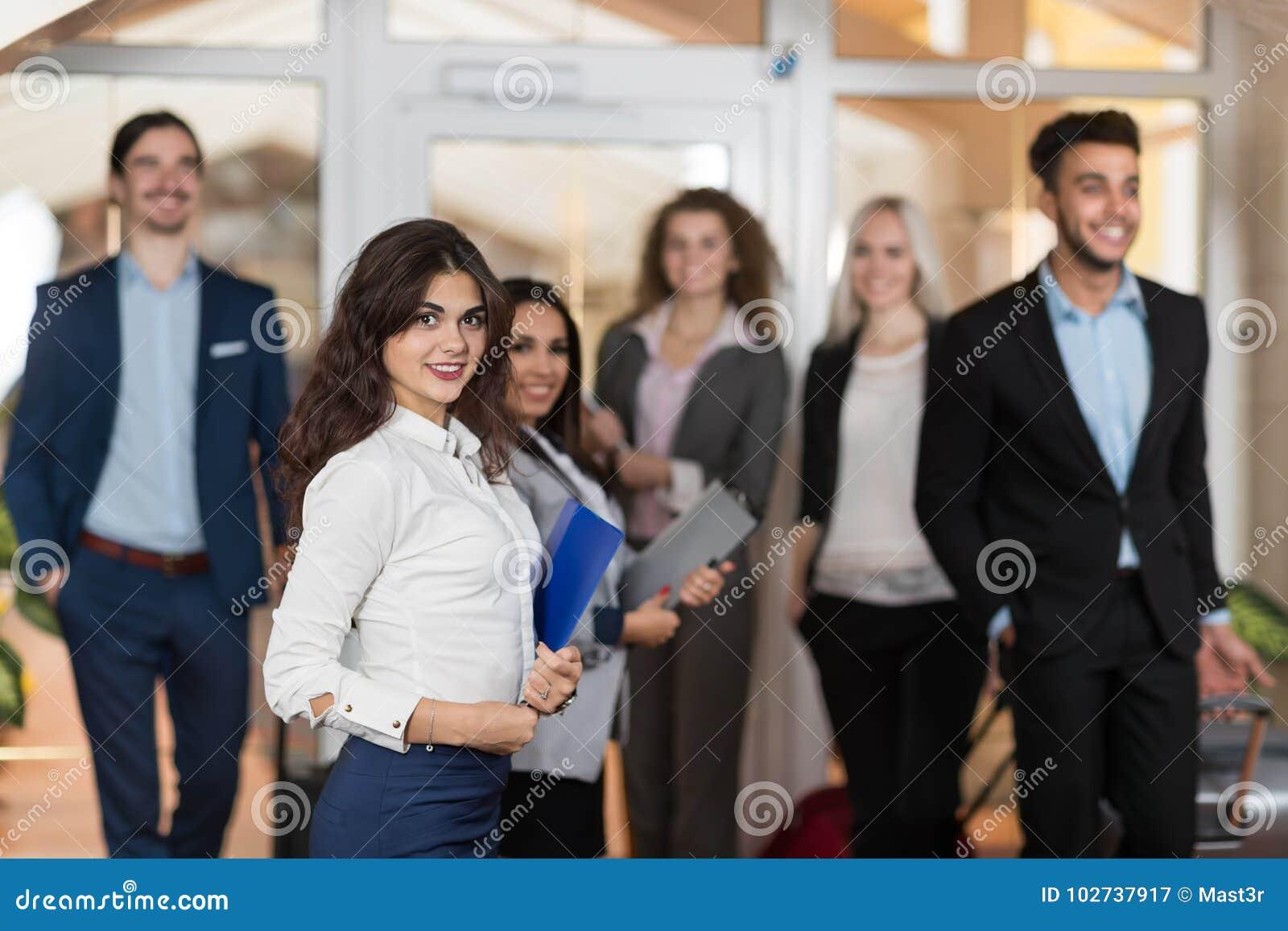 Hotelladministratören Welcome Business People i lobbyen, gäster för grupp för blandningloppBusinesspeople ankommer