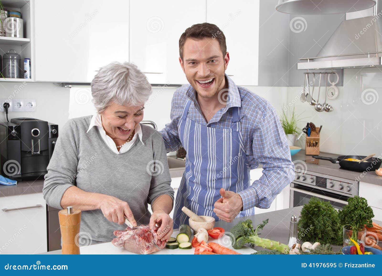Hotellmamma: ung man och äldre kvinna som tillsammans lagar mat griskött