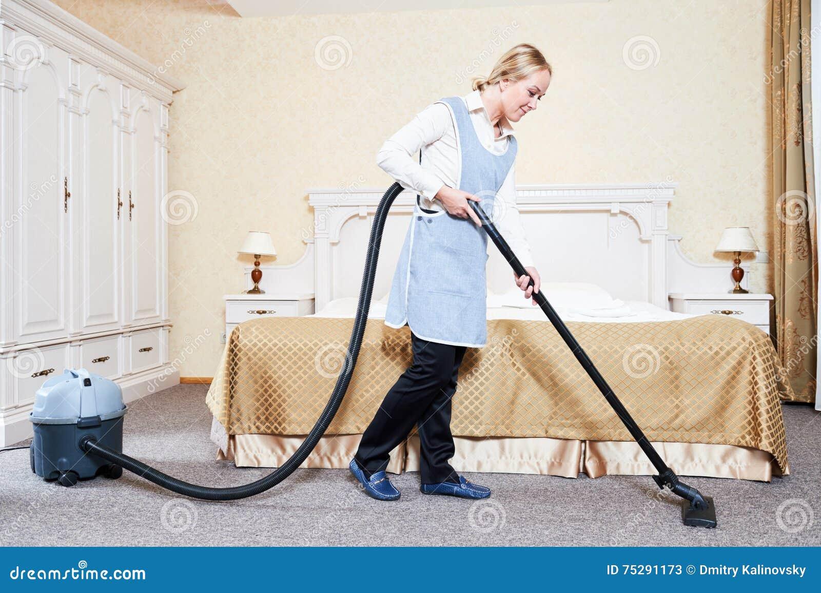 Hotelowa usługa żeński housekeeping pracownik z próżniowym cleaner