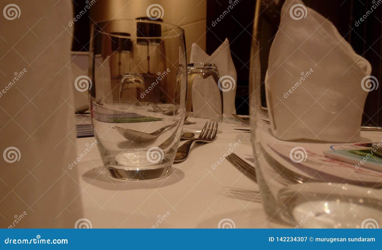 Hotelu stół zakrywający z szkłem woda, jedzenie talerz, rozwidlenie i łyżka w czystym dla nadchodzącego przyjęcia,