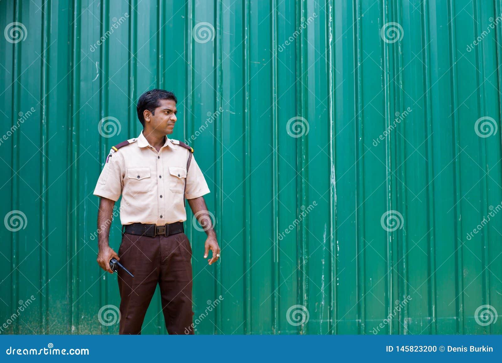 Hotelveiligheidsagent in Sri Lanka tegen een groene omheining