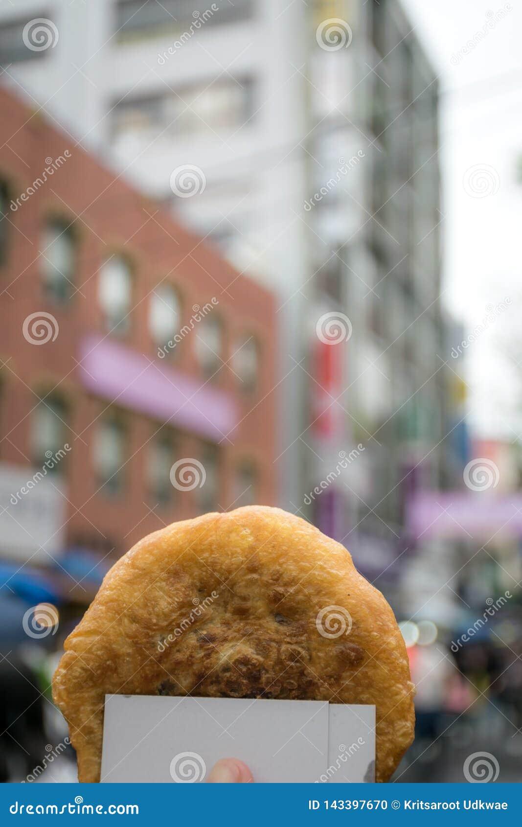 Hotteok o pancake coreano dolce con la città nel fondo