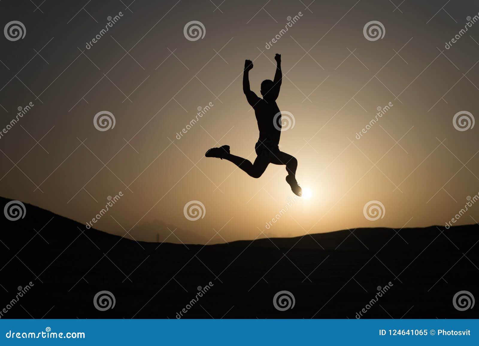 Houd bewegend De motiesprong van de silhouetmens voor de achtergrond van de zonsonderganghemel Dagelijkse motivatie Gezonde perso
