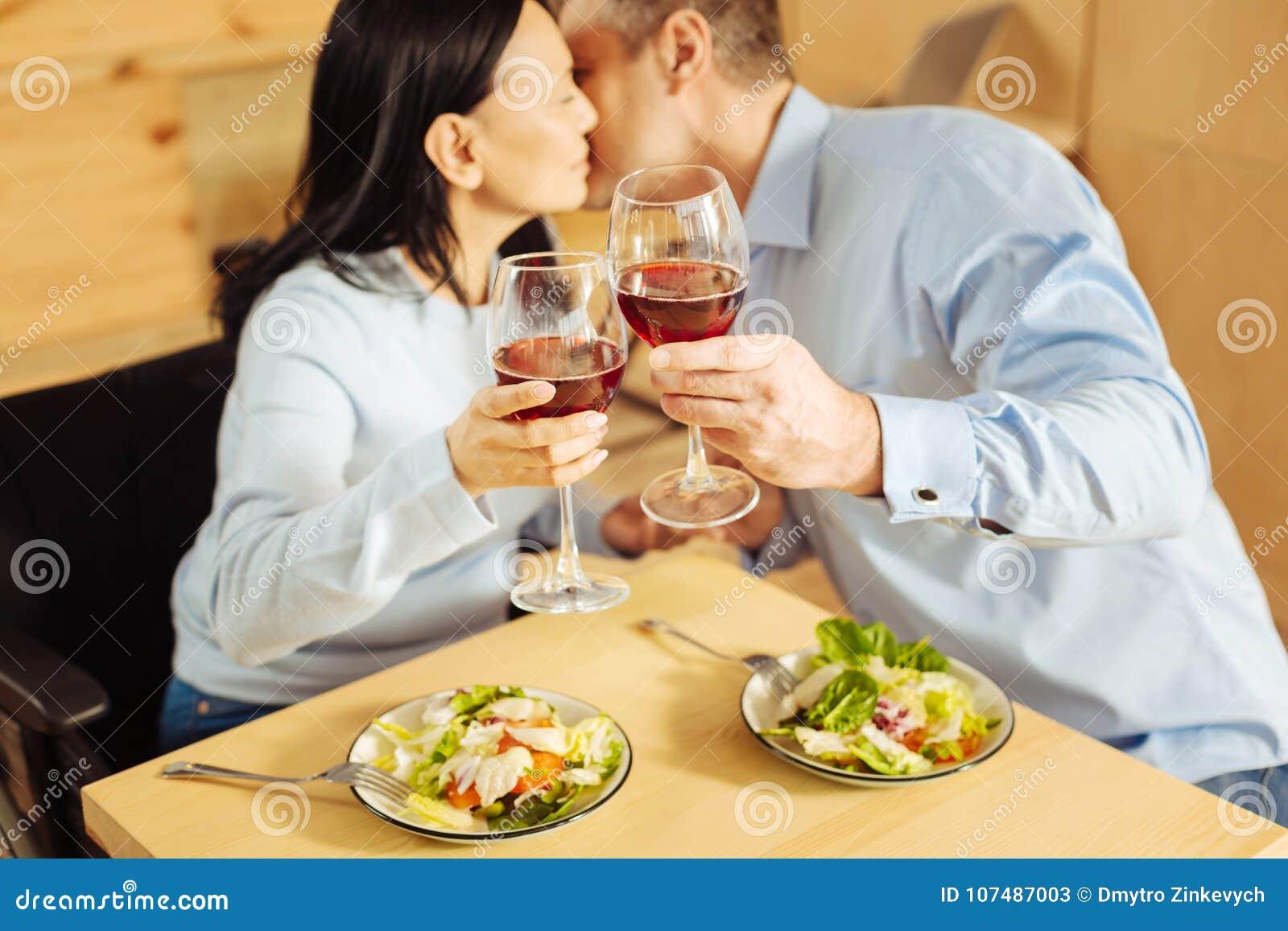 Houdend van paar die en het drinken wijn kussen