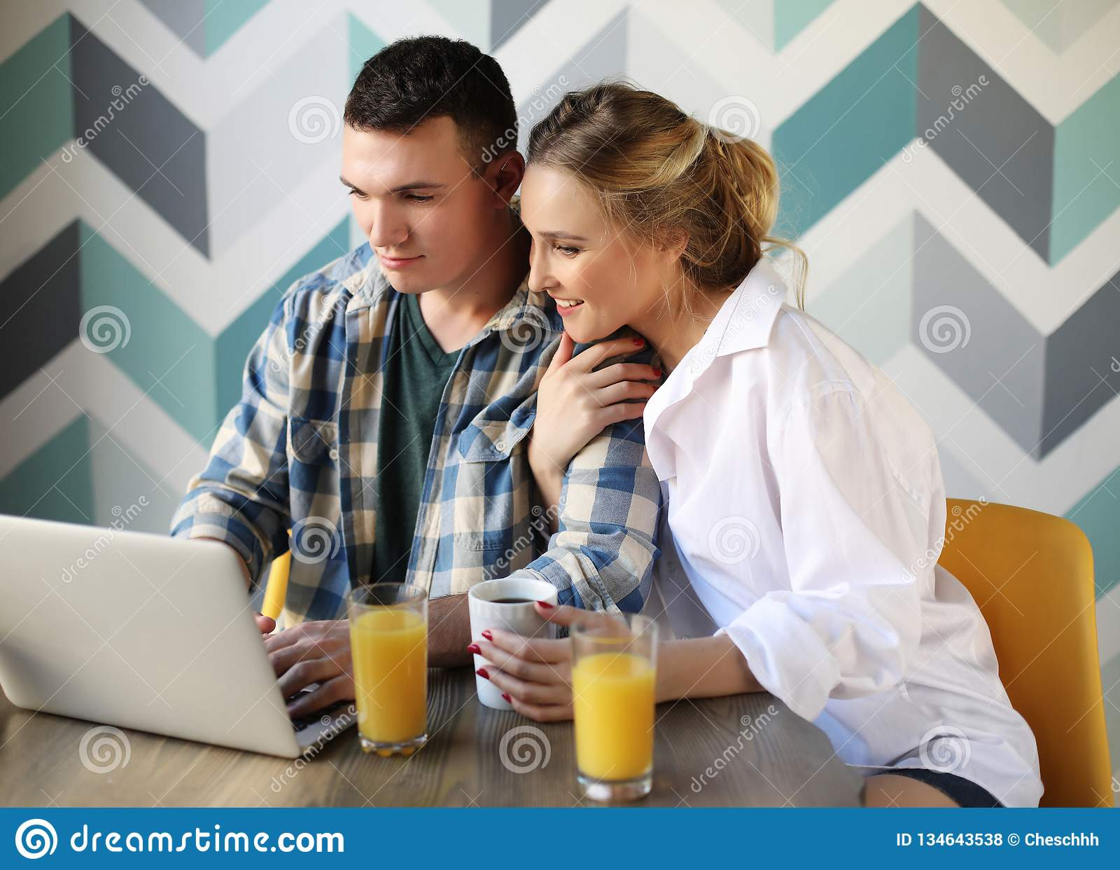 Houdend van paar die ontbijt hebben terwijl het zitten bij de lijst in een keuken thuis en het bekijken laptop computer