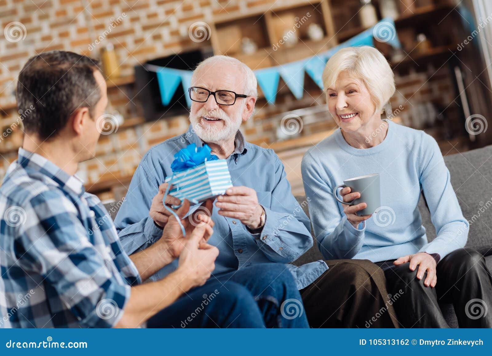 Houdende van zoon die verjaardagsgeschenk geven aan zijn bejaarde vader