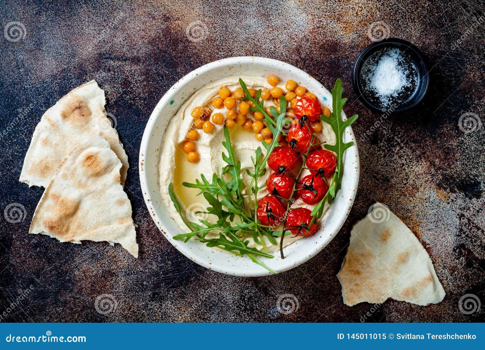 Houmous fait maison avec les tomates-cerises r?ties Cuisine arabe traditionnelle et authentique du Moyen-Orient