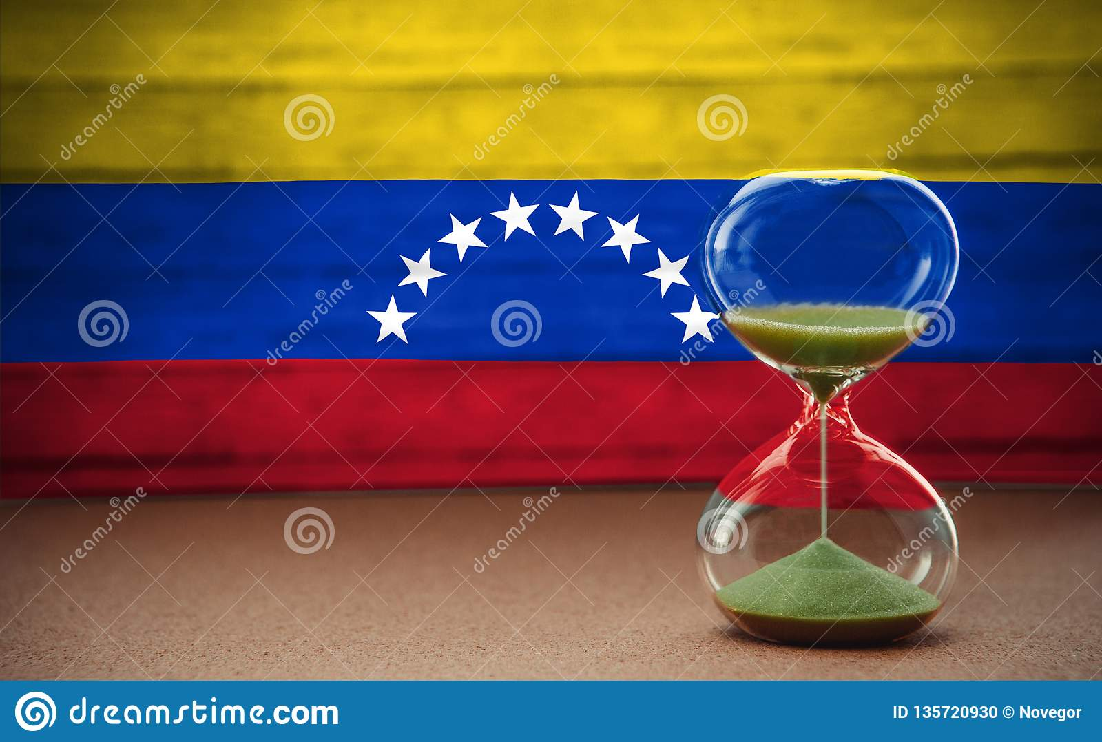 Hourglass on the background of the Venezuela flag, the concept of time and countries, space for text