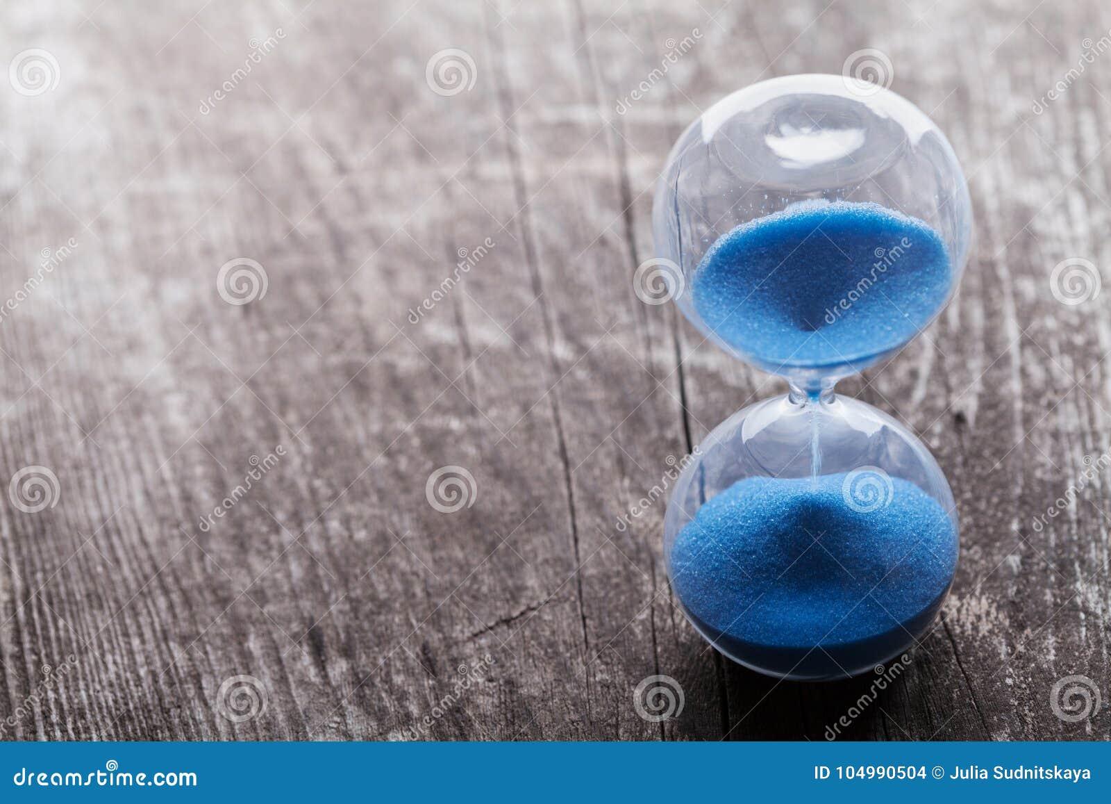 Hourglass lub sandglass na nieociosanym drewnianym stole Czas biega out lub ostatecznego terminu pojęcie