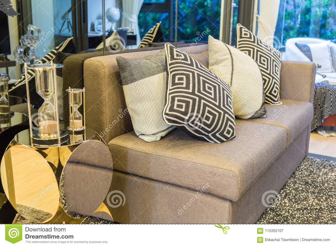 a hourglass side pillows on a brown sofa with a black and white rh dreamstime com