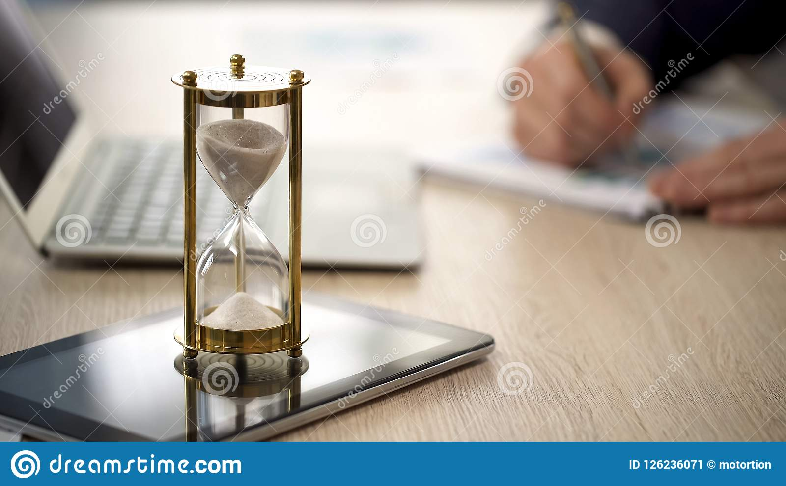 Hourglass standing on table with sand trickling, man working with graphs, data