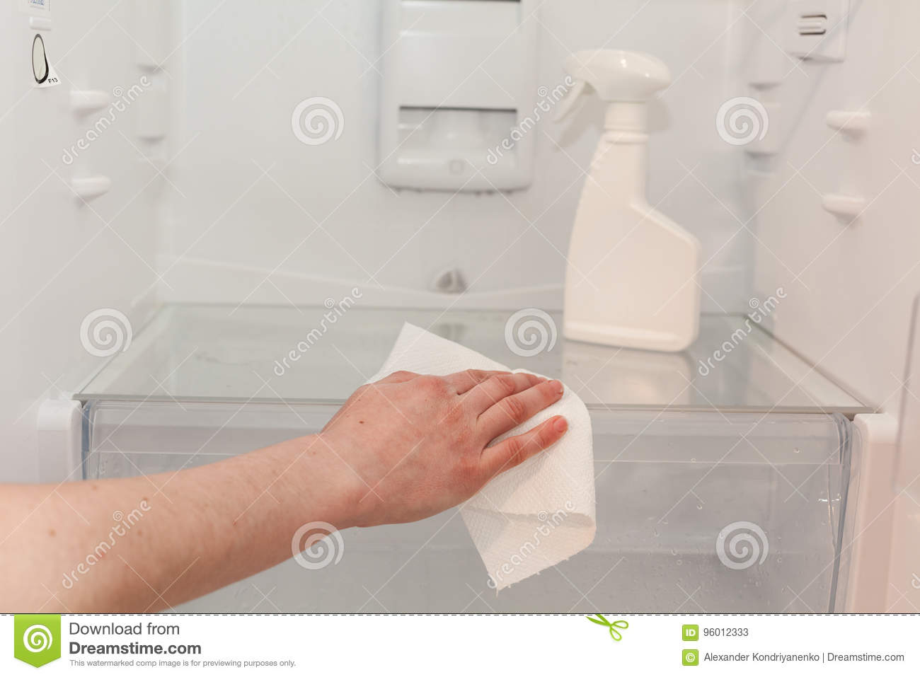 House cleaning - spray bottle with detergents for washing the fridge. The housekeeper wipes the shelves of a clean refrigerator wi