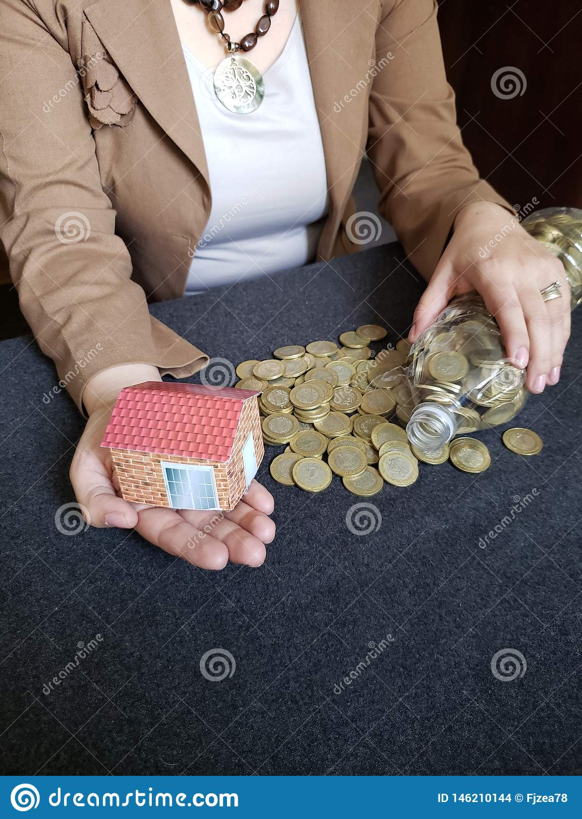 house figure in the hand of a person and coins of savings in mexican pesos