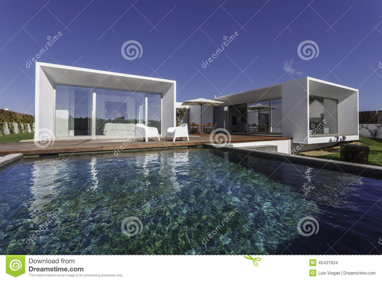 Modern house with garden swimming pool and wooden deck.