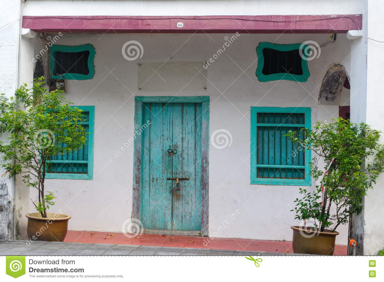 House in George Town, Penang, Malaysia. Mediterranean style exterior. Blue wooden doors and window shutters on old painted wall