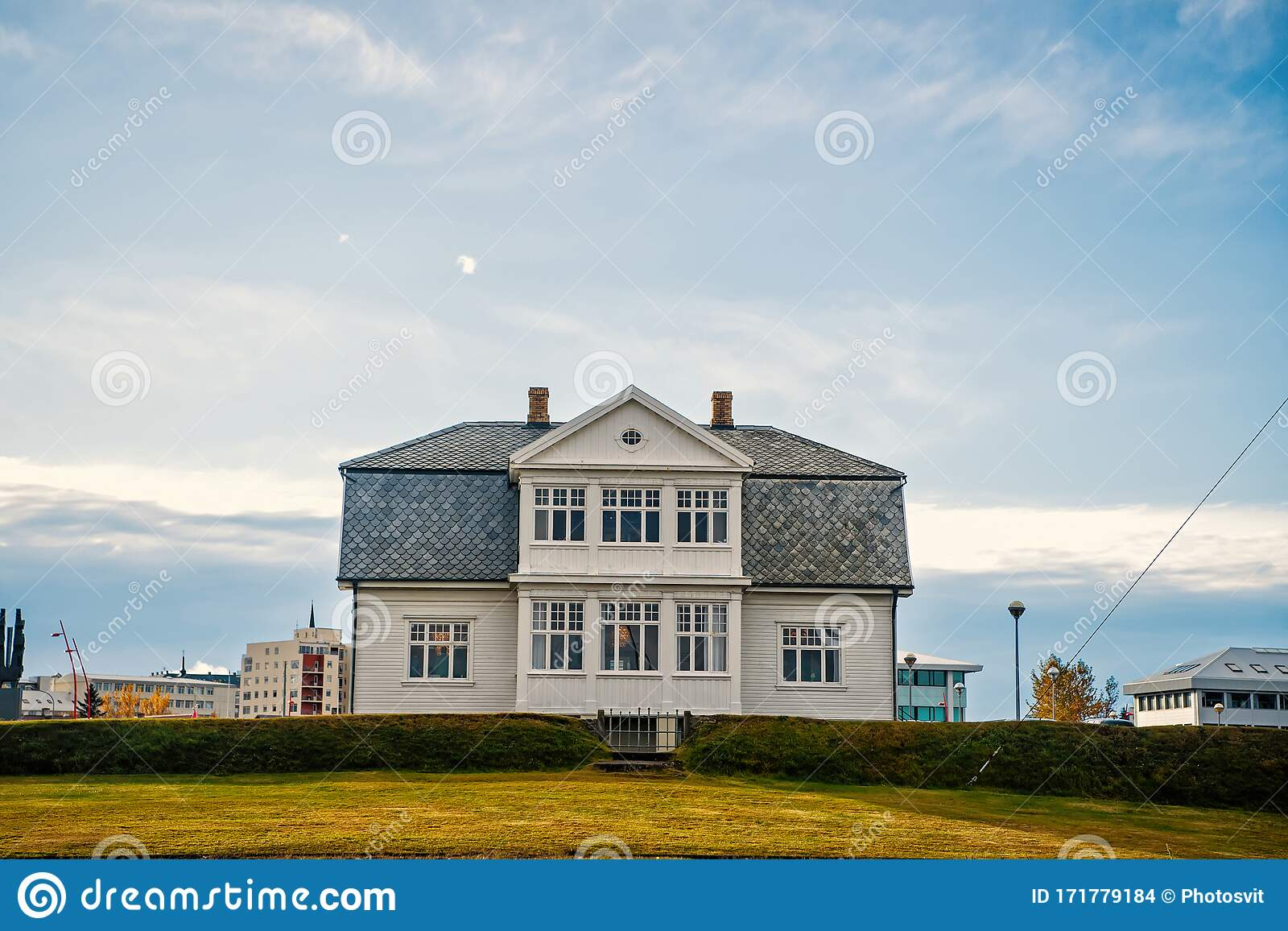 House With Green Lawn On Blue Sky In Reykjavik Iceland