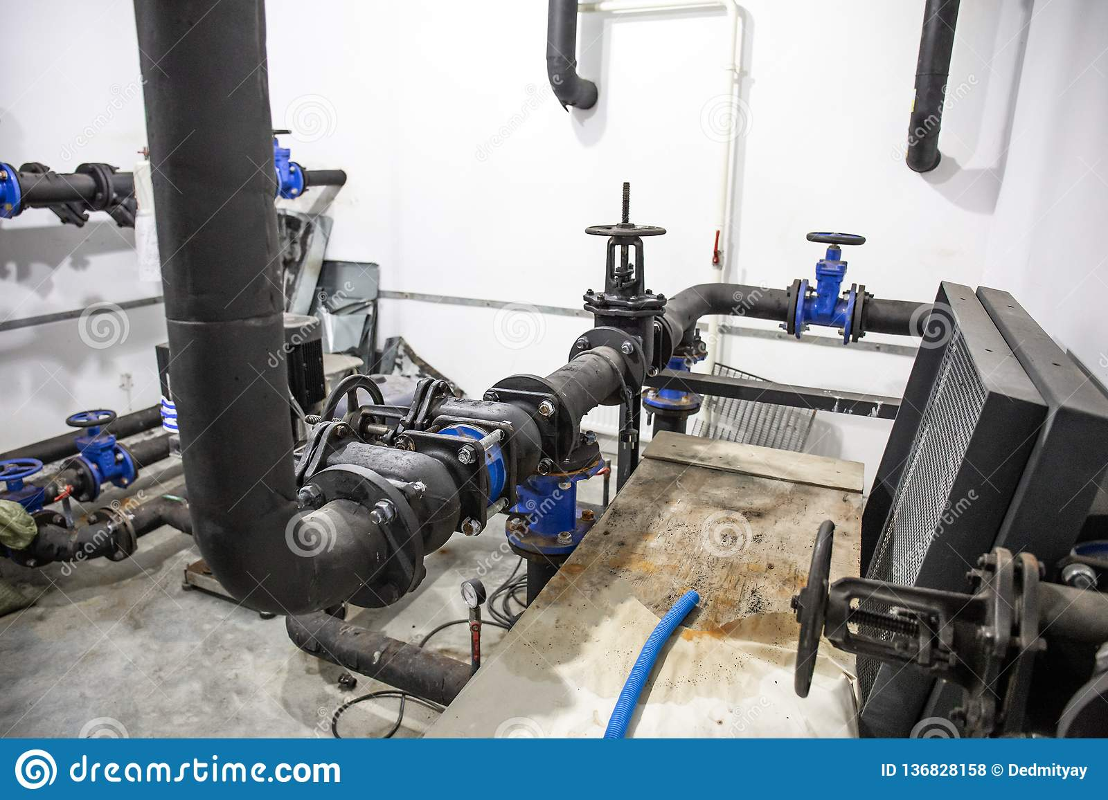 House heating system with many steel and plastic pipes, metal tubes and automated control equipment