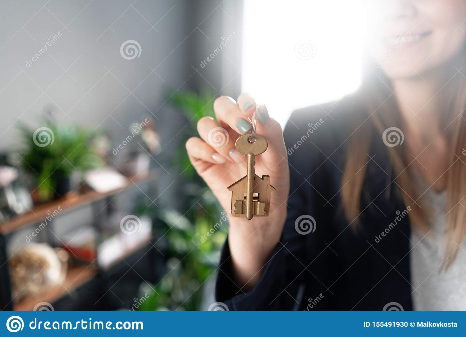 House key rotates on the finger in womans hands. Young pretty woman smiles. Modern light lobby interior. Real estate