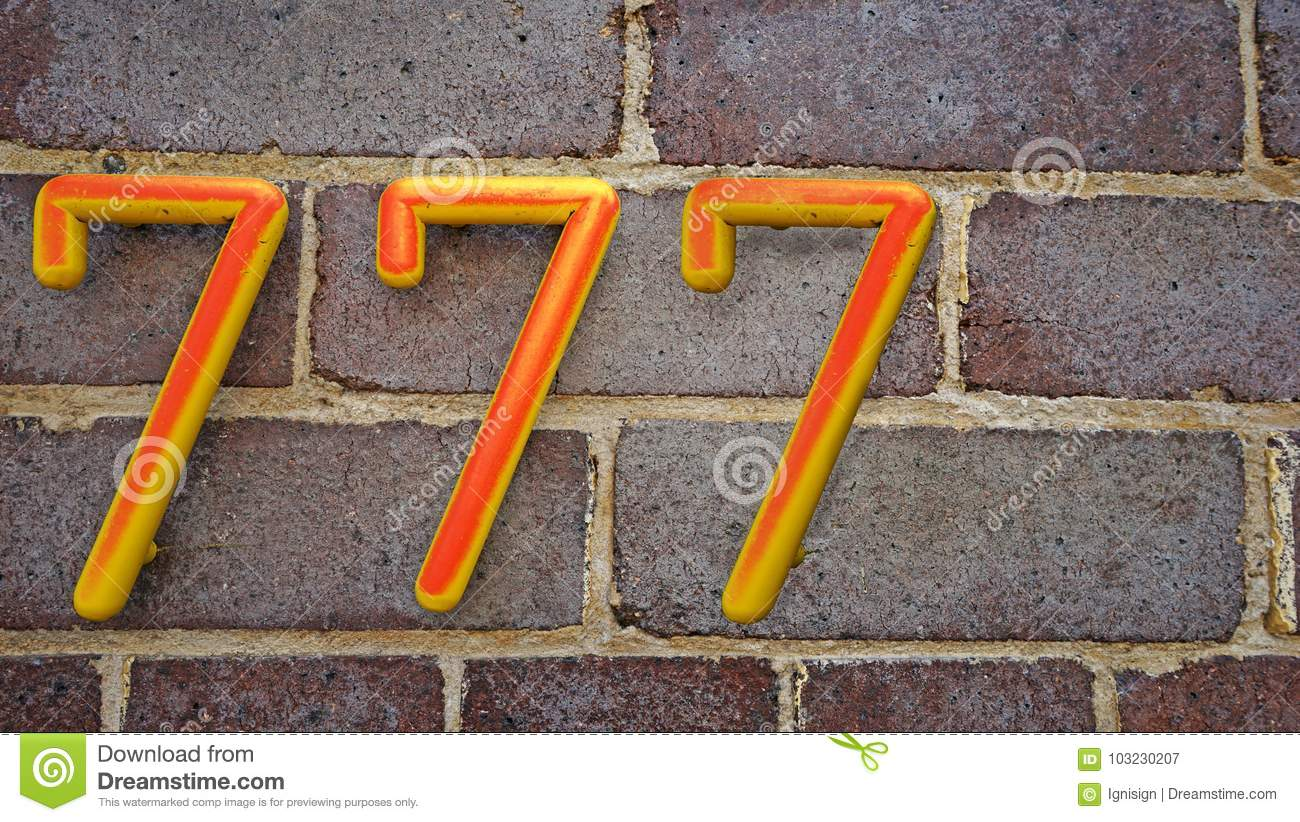 House number seven hundred and seventy seven 777 on brick wall background
