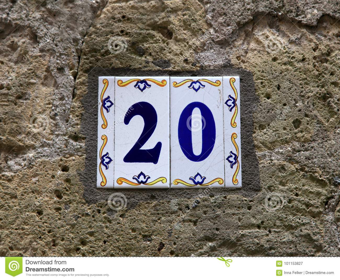 House number twenty 20: ceramic tiles with blue figures on old stone wall.