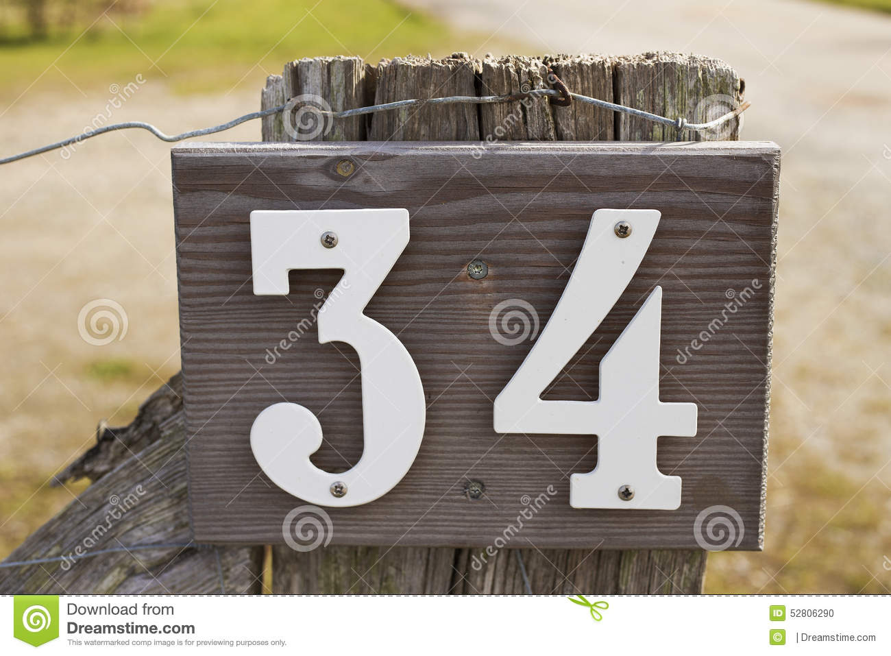 A wooden sign with 'house number 34' in white letters