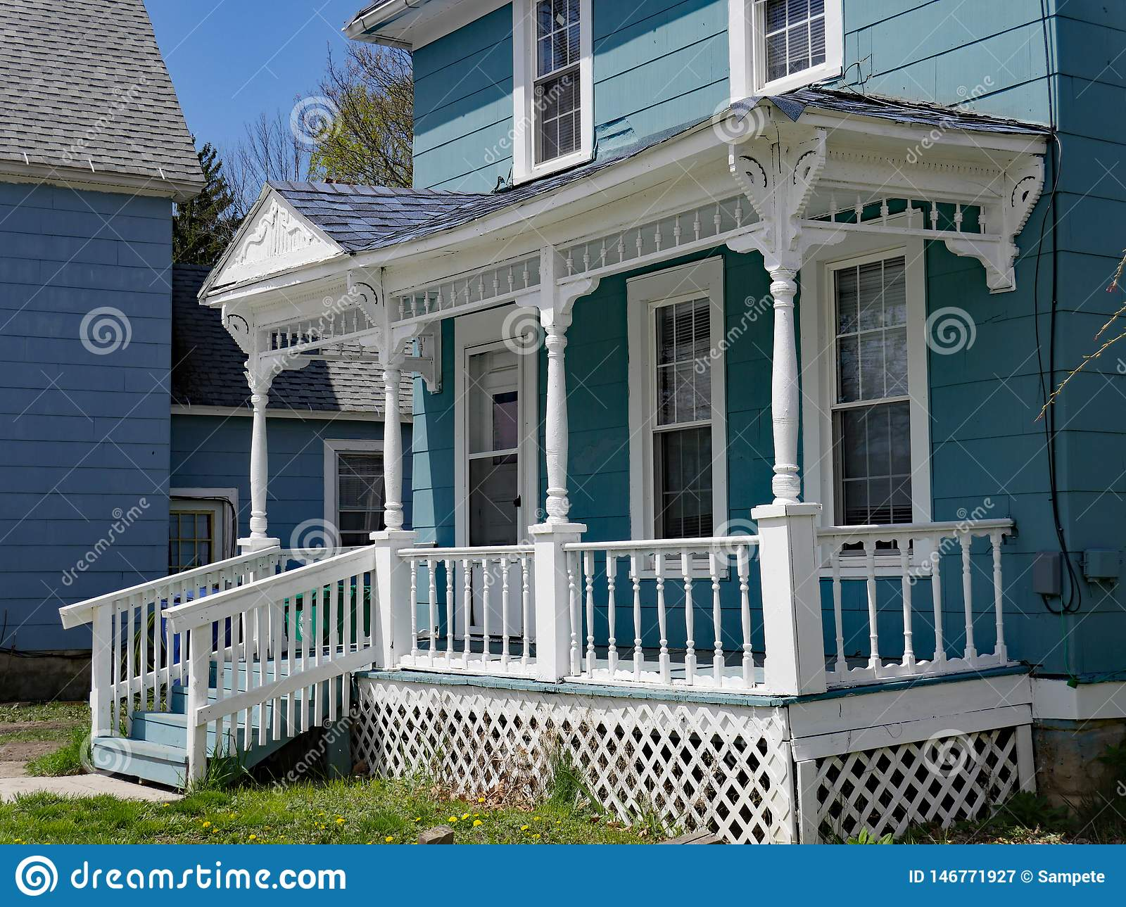 House with old fashioned wood spindle railing on porch