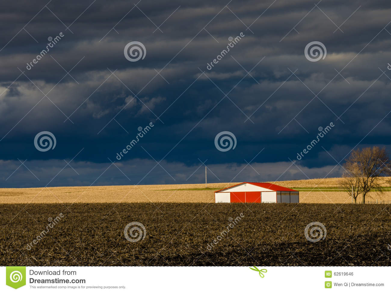 The barn with red roof under storm clouds