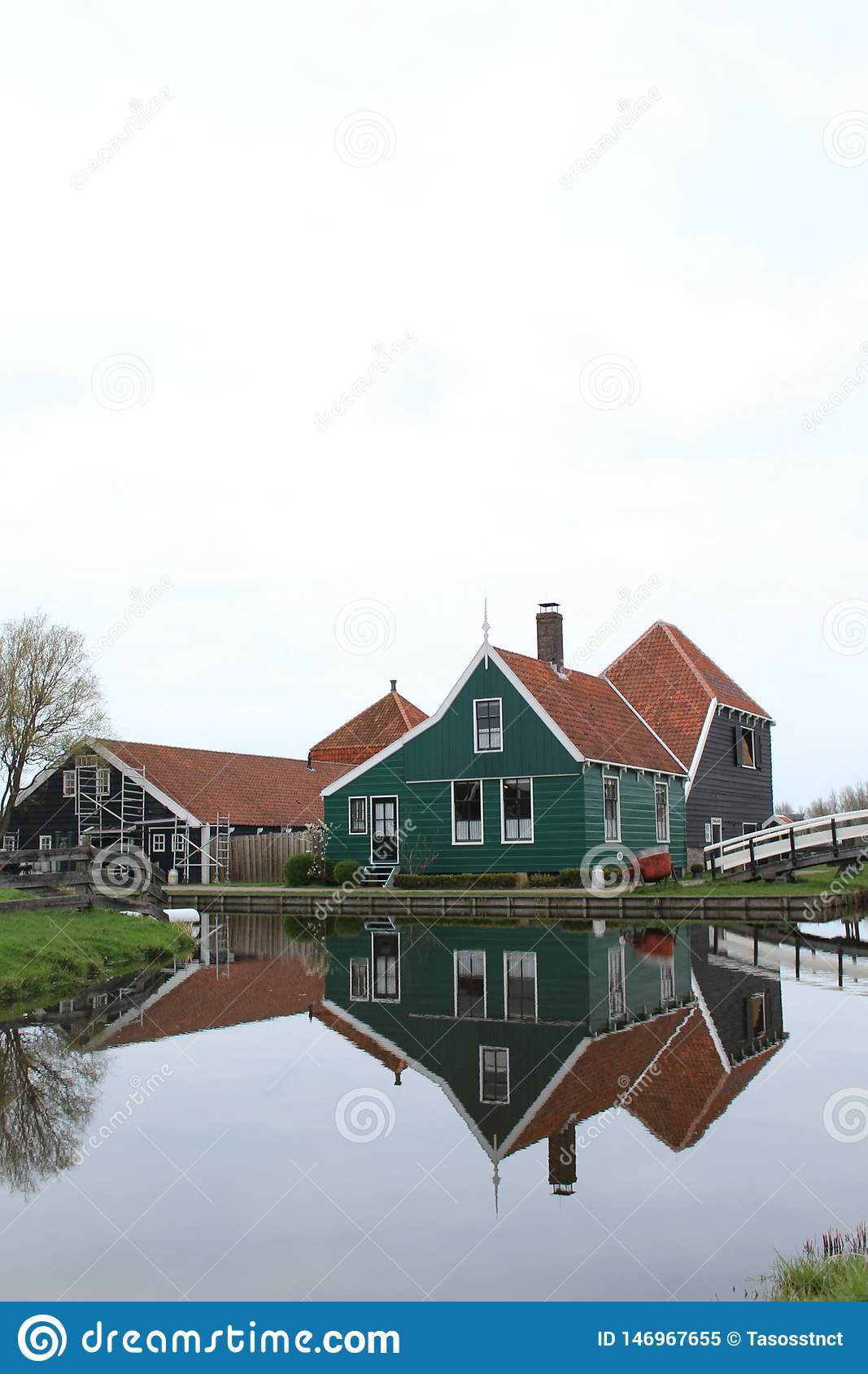 A HOUSE REFLECTING AT THE CALM WATERS OF ZAANSE SCHANS