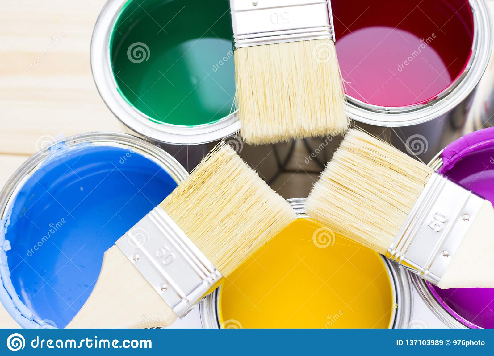 House renovation concept, colorfull paint cans and paintbrushes on wooden background