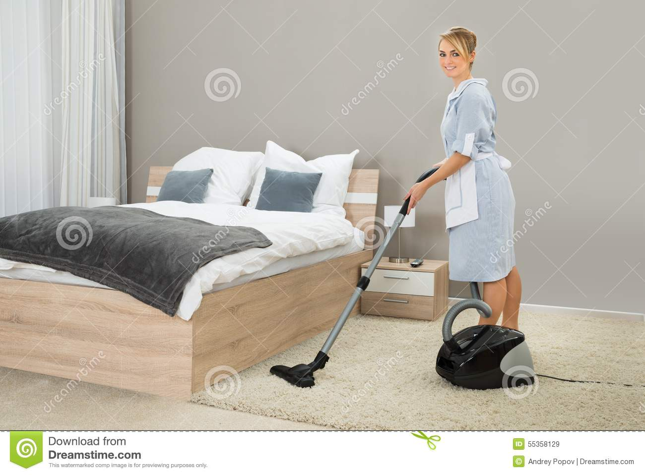 Housekeeper cleaning with vacuum cleaner