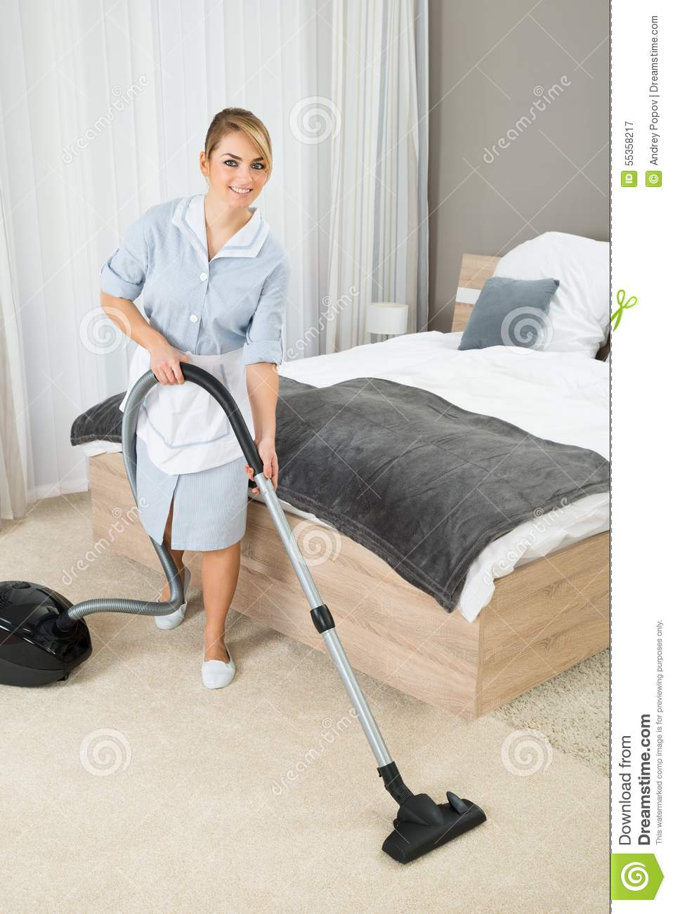 Housekeeper Cleaning With Vacuum Cleaner Stock Photo