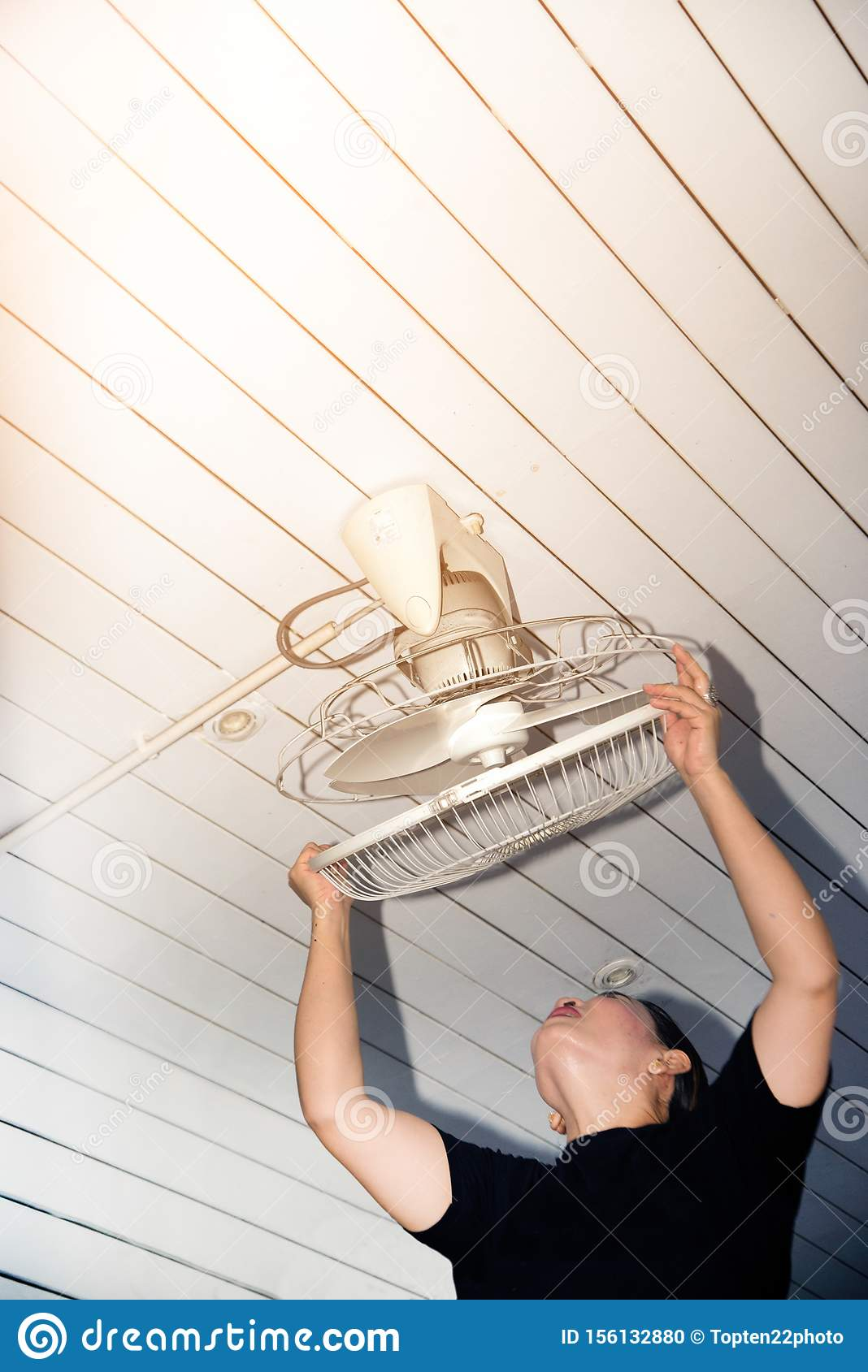 The Maidservant Is Installing And Cleaning The Ceiling Fan